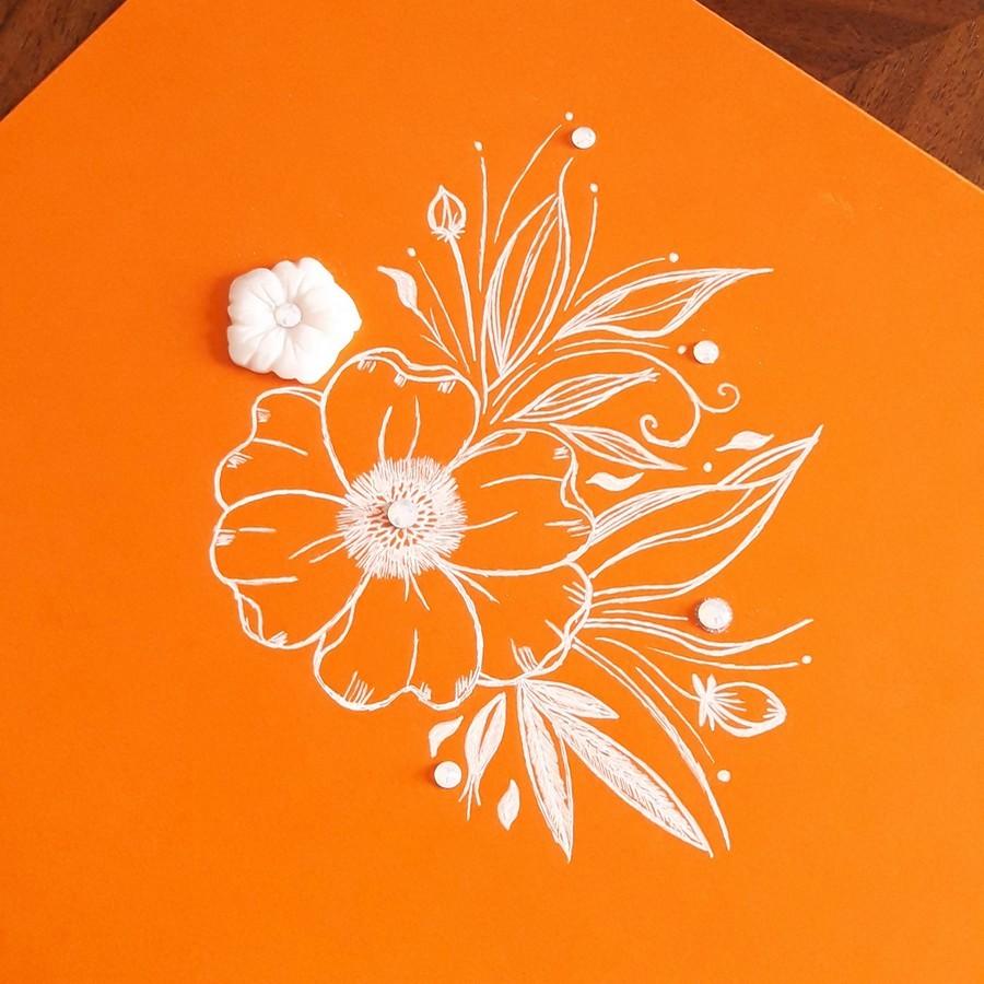 Dessin encre blanche sur feuille orange